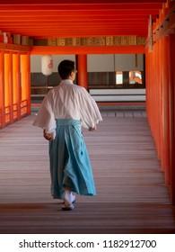"Miyajima/Japan - August 8 2018: Monk at Itsukushima Shrine, Japan. Itsukushima Shrine is a Shinto shrine on the island of Itsukushima, best known for its ""floating"" torii gate."