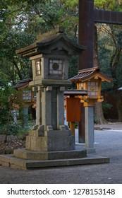 Miyazaki, Japan - November 4, 2018: Old stone lantern and new ones at the Miyazaki Jingu shrine grounds