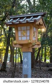 Miyazaki, Japan - November 4, 2018: New and modern stone lantern decorated with a golden crysanthemum at the Miyazaki Jingu shrine grounds