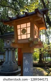 Miyazaki, Japan - November 5, 2018: Modern stone lantern decorated with a golden chrysanthemum at the Miyazaki Jingu shrine grounds at dusk