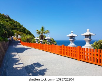 Miyazaki, JP - APRIL 8, 2019: Perspective walkway with many orange fences and white stones inside Udo-jingu Shinto Shrine, the famous sightseeing in Nichinan, the birthplace of Emperor Jimmu's father.