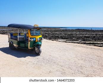 Miyazaki, JP - APRIL 8, 2019: One colorful Tuk-Tuk trishaw taxi from Thailand running on a sandy street near a rocky coastline at Aoshima Island.