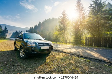 Mizhhirya, Ukraine - OCT 21, 2017: Hyundai Tucson SUV on countryside road in foggy mountains. lovely transportation scenery at sunrise in autumn. travel by car concept