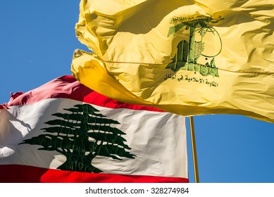 "MLEETA - SEPTEMBER 26: A Hezbollah flag flies with the Lebanese flag. The Arabic text reads ""Then surely the party of Allah are they that shall be triumphant"" and ""The Islamic Resistance in Lebanon."""