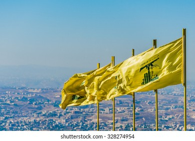 "MLEETA - SEPTEMBER 26: Hezbollah flags over southern Lebanese land. The Arabic text reads ""Then surely the party of Allah are they that shall be triumphant"" and ""The Islamic Resistance in Lebanon."""
