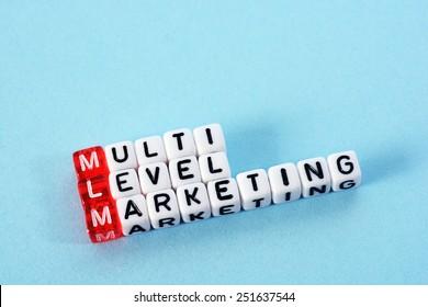 MLM Multi Level Marketing   written  on  cubes on blue  background