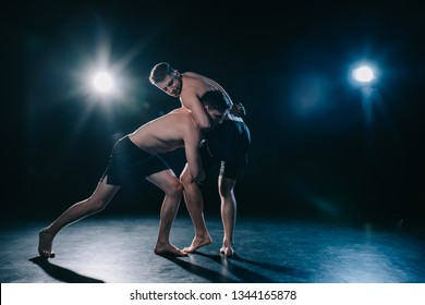 mma fighter doing chokehold and joint lock to another sportsman in stance during wrestling training