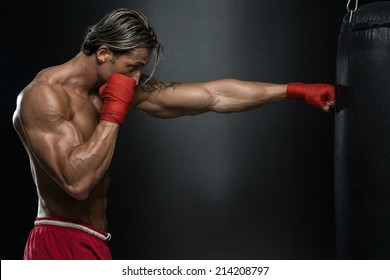 MMA Fighter Practicing With Boxing Bag - A Man With A Tattoo In Red Boxing Gloves - Boxing On Black Background - The Concept Of A Healthy Lifestyle - The Idea For The Film About Boxing