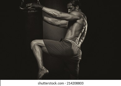 MMA Fighter Practicing Some Kicks With Punching Bag - A Man With A Tattoo In Red Boxing Gloves - Boxing On Black Background - The Concept Of A Healthy Lifestyle - The Idea For The Film About Boxing