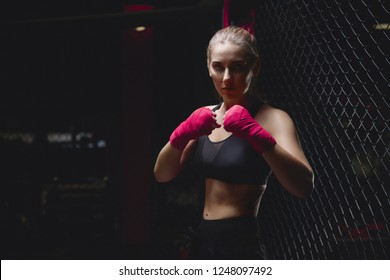 MMA girl in sports uniform ready to fight Boxing ring defense of women from violence, pink bandages on his fists, combat readiness