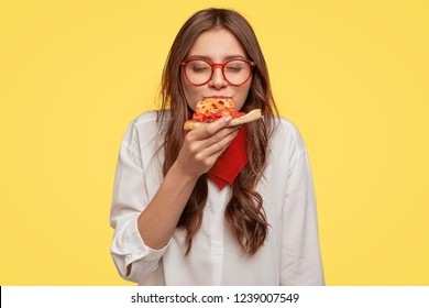 Mmm, so delicious! Dark haired pretty woman eats slice of Italian pizza, keeps eyes closed from pleasure, enjoys nice taste, wears glasses and shirt, isolated over yellow background. Eating concept