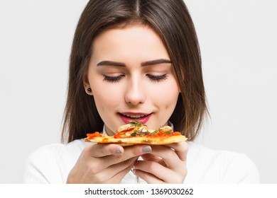 Mmm, so delicious! Dark haired pretty woman eats slice of Italian pizza, keeps eyes closed from pleasure, enjoys nice taste, isolated over white background.