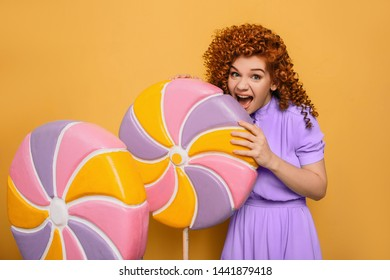 mmm yummy it is very sweet lollipop. Emotional curly haired woman bite off piece candy on yellow