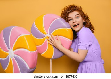 mmm yummy it is very sweet lollipop. curly red-haired woman hugging candy on yellow background
