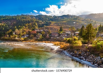 Mo Chhu River on a nice sunny day, Punakha, Bhutan. View from the wooden cantilever bridge near Punakha Dzong to river, houses of Punakha city and Himalaya mountains covered with forest.