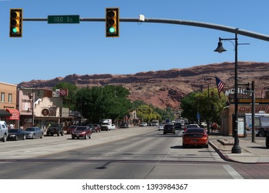 Moab, UT - June 13, 2018. A sharp image of downtown Moab on a crystal clear day. Bright blue skies and red and brown hills in the background help frame the downtown streets, trees and retail stores.