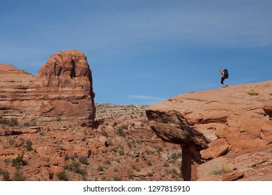Moab, Utah / USA 10/22/2017  A woman wearing a large backpack walks to the edge of an overlook to see the scenery in the tourist destination desert of Moab Utah.