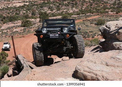 Moab , Utah , USA, April 23, 2019: Black Rubicon Jeep coming up the Widow Maker obstacle on the Metal Masher off road Jeep trail .