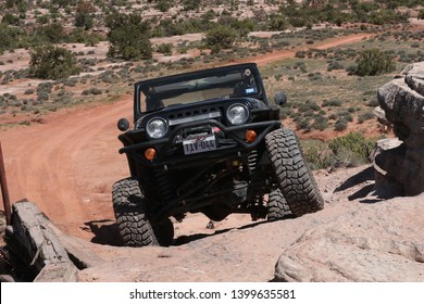 Moab Utah, USA, April, 23, 2019 : Black Rubicon Jeep coming up the Widow Maker obstacle on the Metal Masher off road Jeep trail during Easter Safari.