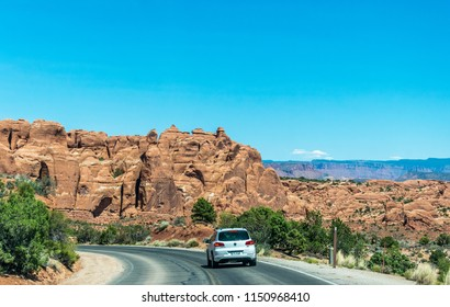 Moab, Utah / USA - June 25 2017: Highway and tourist transport in Arches National Park, Utah, USA. Eroded limestone rocks and desert landscape of the southwest of the USA