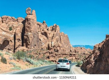 Moab, Utah / USA - June 25 2017: Modern new highway and tourist transport in Arches National Park, Utah, USA. Eroded limestone rocks and desert landscape of the southwest of the USA
