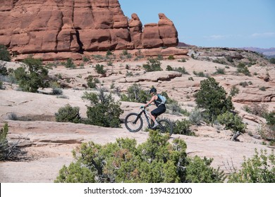 Moab Utah USA,  May 3, 2019: Mountain biker female woman riding her fat tire bike on slickrock in scenic Moab