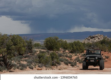 Moab, Utah,USA,April,21,2019: Black Rubicon Jeep on Dome Plateau Jeep trail with storm clouds in the background.