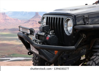 Moab, Utah,USA,April,21,2019: Close up of a Black Rubicon Jeep with  a mountain view from Dome Plateau overlook in the background.