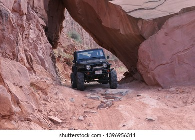Moab, Utah,USA,April,22,2019 :Black Rubicon Jeep going under a giant boulder on Long Canyon Jeep trail.