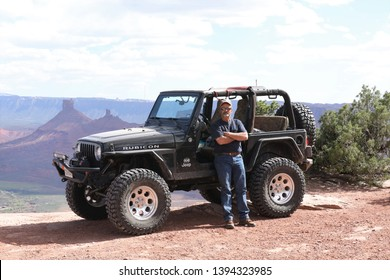 Moab,Utah,USA,April,21,2019: A guy standing beside his black Rubicon Jeep on Dome plateau Jeep trail.