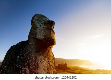 Moai looking at sea with bright blue sky and orange sea in background