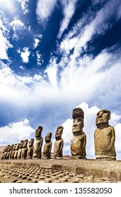 Moais standing on ahu with dramatic clouds in background in Easter Island