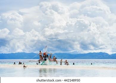 Moalboal. Cebu. Philippines. - 24 june 2016: Asian people with tourists getting fun and rest on the boat in tropical sea under scenic cloudy sky