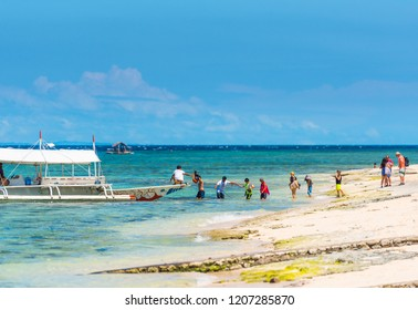 MOALBOAL, PHILIPPINES - FEBRUARY 20, 2018: Boat and a group of tourists near the shore. Copy space for text