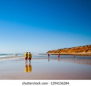 MOANA BEACH, ADELAIDE, SOUTH AUSTRALIA, JANUARY 2019; Surf Lifesavers patrol the beach, one pointing to the surf.