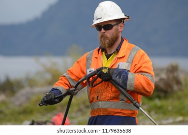 MOANA, NEW ZEALAND, OCTOBER 27, 2017: An unidentified engineer rigs up a water blaster for cleaning up at an oil well in preparation for capping the well.