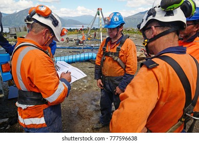 MOANA, NEW ZEALAND, OCTOBER 27, 2017: The safety officer conducts a safety meeting at an abandoned oil well (behind the group) before permitting workers into a confined space.