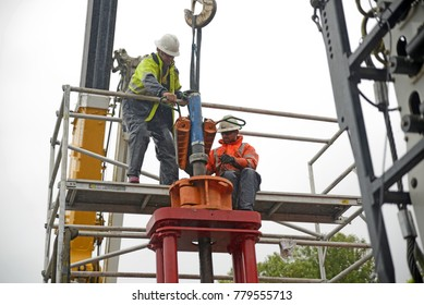 MOANA, NEW ZEALAND, OCTOBER 27, 2017: Engineers work in the rain to remove the steel casing from an oil well that is being plugged and abandoned.