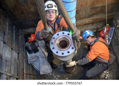 MOANA, NEW ZEALAND, OCTOBER 27, 2017: Engineers place a new flange on top of an oil well in preparation for capping the well. They are working in a ventilated confined space.
