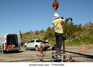 MOANA, NEW ZEALAND, OCTOBER 27, 2017: An oil well engineer directs a crane operator to position a pulley for the wireline during an operation to log the steel casing inside an abandoned oil well.
