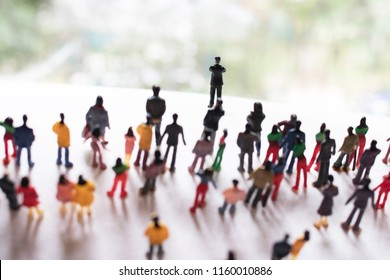 Mob, crowd, or community of people follows one person up a hill. Big group follows a leader. Business people working towards a common goal. Crowd of unrecognizable humans working together,