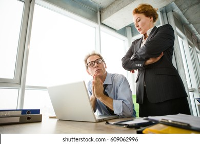 Mobbing, stress, work, scandal concepts. Low view of angry boss woman standing near her worker and listening to his explanations.