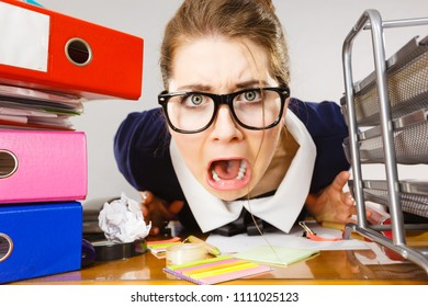 Mobbing at work, bad job relations concept. Depressed businesswoman being sad and tired sitting working at desk full off documents in binders.