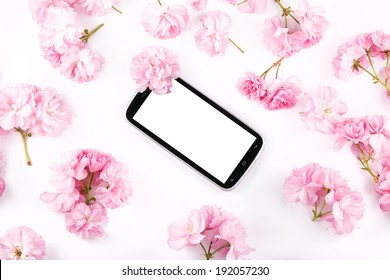 Mobil smart phone surrounded by pink cherry flowers on light bac