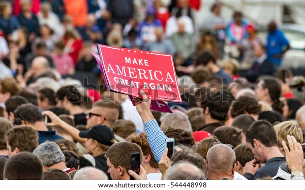 "Mobile, Alabama - 12/17/2016:  A Trump supporter holds up a ""Make America Great Again"" sign in the crowd as US President-elect Donald J. Trump prepares to enter the stage at Ladd-Peebles Stadium."