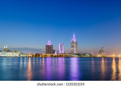 Mobile, Alabama, USA downtown city skyline on the Mobile River at twilight.