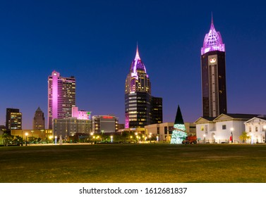 Mobile, AL/USA - January 7, 2020: Skyline of downtown Mobile in Alabama with the three tallest city skyscrapers illuminated with neon lights in the evening. Mobile is a city on Gulf of Mexico coast.