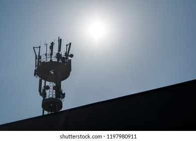 Mobile antenna on the roof of a building against gray sky and sun. Broadcasting and network communicators, receivers. Modern phone and communication technology. GSM antennas.