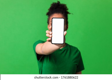 Mobile App Advertising. African woman showing blank cellphone screen, mockup, selective focus, green studio wall