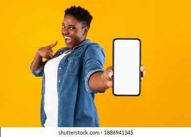 Mobile Application Ad. Aufgeregt afrikanische Frau mit einem leeren Bildschirm für das Telefon, die eine App auf gelbem Studio-Hintergrund steht, lächelt der Kamera zu. Handy-Display-Mock-up, prüfen Sie diese Apps